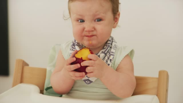 I want a refund! They said this would be sweet 4K video footage of an adorable baby girl eating a sour piece of fruit at home tasting stock videos & royalty-free footage