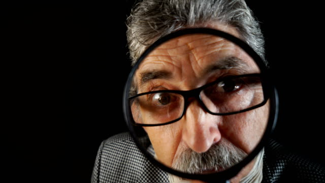 I want to see you better Close-up video of senior man peering through a magnifying glass. magnifying glass stock videos & royalty-free footage