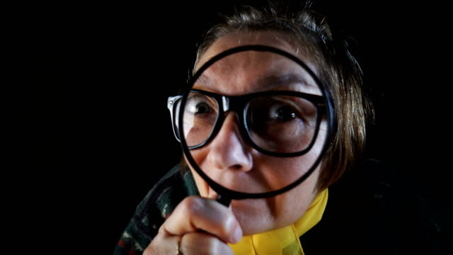 I want to see you better Close-up video of senior woman peering through a magnifying glass. magnifying glass stock videos & royalty-free footage