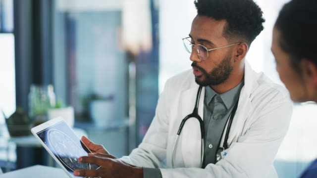 I want you to take a look at this... 4k video footage of a handsome young doctor using a digital tablet during a consultation with a patient in his office black people stock videos & royalty-free footage
