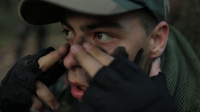 War camouflage Soldier outdoors in forest,applying face paint on his face hiding stock videos & royalty-free footage