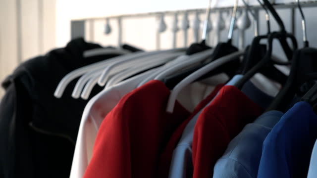wardrobe hanger with multi-colored clothes in the store. colorful outfits hang on a hanger. a woman's hand takes a hanger with a red dress. pulls out of the closet fullhd - вешалка стоковые видео и кадры b-roll