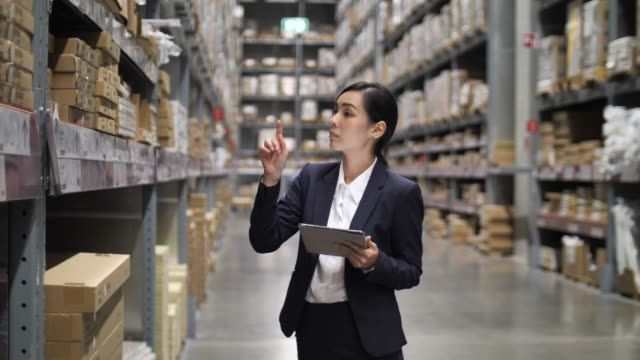 warehouse businesswoman manager using her digital tablet in warehouse - ecommerce video stock e b–roll