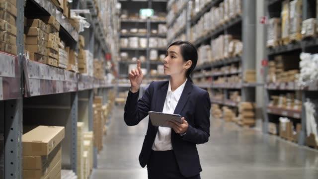 vídeos de stock, filmes e b-roll de gerente da mulher de negócios do armazém usando sua tabuleta de digitas no armazém - comércio eletrônico