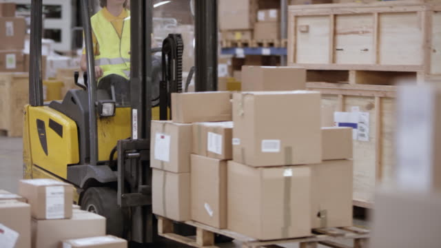 Warehouse employee driving a reach truck with packages on a pallet through a warehouse Wide handheld shot of a male warehouse employee driving an electric reach truck full of packages across the warehouse. Shot in Slovenia. forklift stock videos & royalty-free footage
