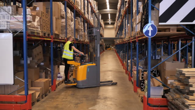 Warehouse employee in reflective uniform driving forklift Working in warehouse - supply chain management and wholesale process scandinavia stock videos & royalty-free footage