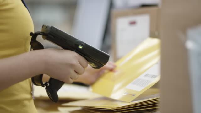 PAN Warehouse employee scanning envelopes with a handheld barcode scanner Medium handheld shot of a warehouse employee scanning envelopes with a handheld barcode scanner in her hand. Shot in Slovenia. post structure stock videos & royalty-free footage
