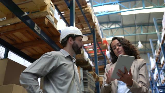 vídeos de stock, filmes e b-roll de funcionários do armazém discutindo cronogramas de entrega - gerente