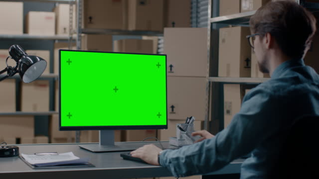Warehouse Inventory Manager Works on a Green Mock-up Screen Computer while Sitting at His Desk. In the Background Shelves Full of Cardboard Box Packages Ready For Shipping. video