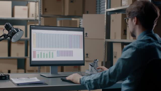 lager-inventar-manager arbeitet mit einer tabellenkalkulation auf einem personal computer sitzend an seinem schreibtisch. im hintergrund regale voller karton-pakete für den versand bereit. - post it stock-videos und b-roll-filmmaterial