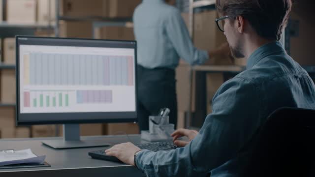 lagerchefen lagret fungerar med ett kalkylblad på en dator medan du sitter på hans skrivbord. i bakgrunden hyllor fulla av kartong paket redo för frakt. - accounting bildbanksvideor och videomaterial från bakom kulisserna