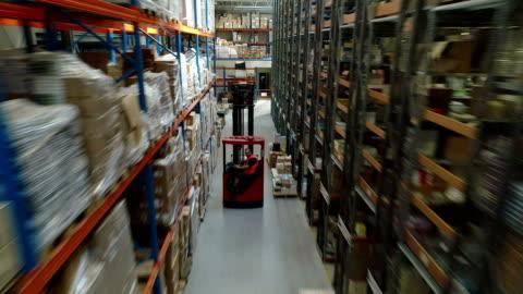 vídeos de stock e filmes b-roll de warehouse logistic center. worker driving on a forklift - consumismo