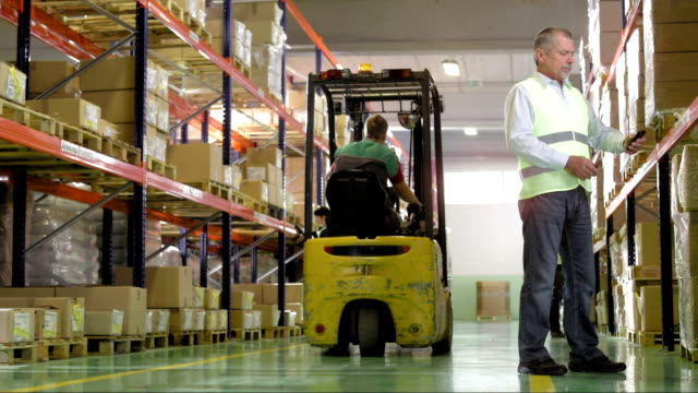Warehouse Manager Scans Codes With Smartphone HD1080p: DOLLY shot of an adult male supervisor using a smartphone for scanning bar codes from boxes in the warehouse. In the background two other warehouse employees doing an inventory and a forklift operator placing the loaded pallet onto the rack for storage. forklift stock videos & royalty-free footage