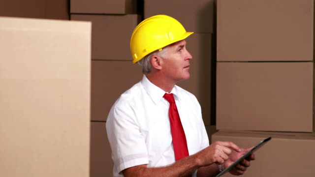stockvideo's en b-roll-footage met warehouse manager sitting using his tablet pc - overhemd en stropdas