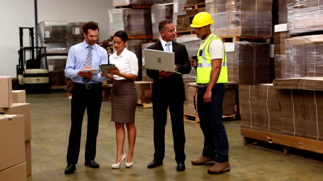 Warehouse managers and worker talking video