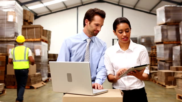 Warehouse managers looking at tablet pc and laptop video