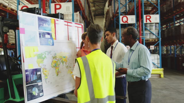 Warehouse staff in discussion at an information board 4k