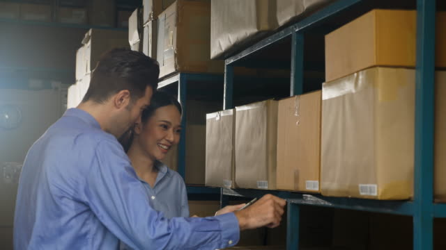 Warehouse worker check and discuss products stock.