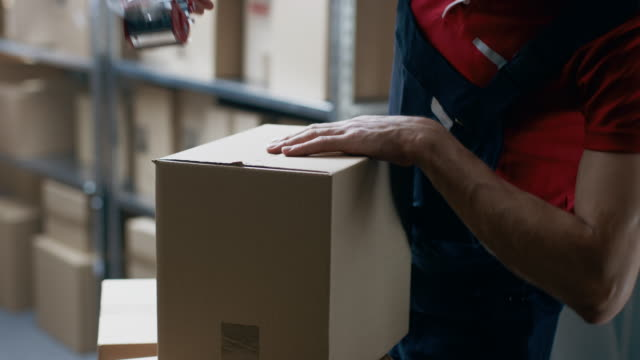 vídeos de stock e filmes b-roll de warehouse worker checks and seals cardboard box ready for order shipment. - cardboard box