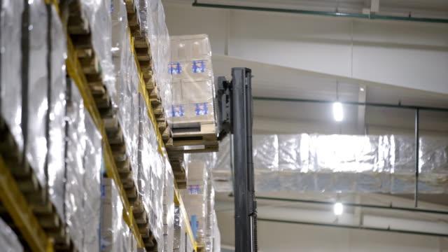 Warehouse worker driver loading cardboard boxes by forklift stacker loader furnirure storage boards - video