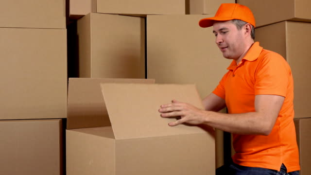 Warehouse worker in orange uniform packaging big carton with duct tape gun. Multiple boxes background. FullHD video video