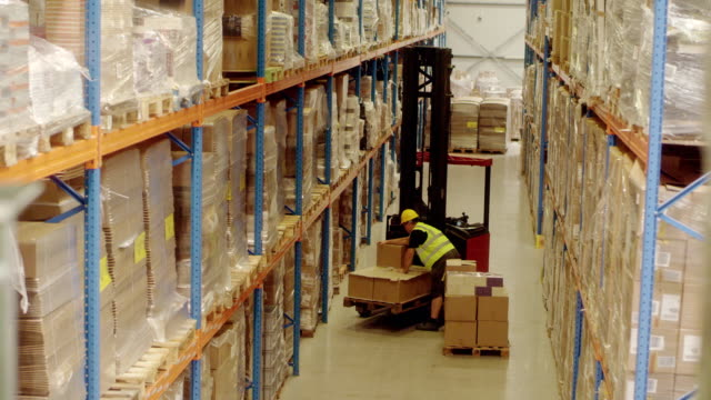 Warehouse worker picking packages with a forklift video