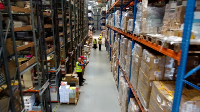 Warehouse worker walking among shelves. Supervising. Drone point of view