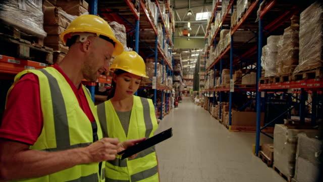 stockvideo's en b-roll-footage met magazijn werknemers controleren inventaris met tablet - warehouse worker