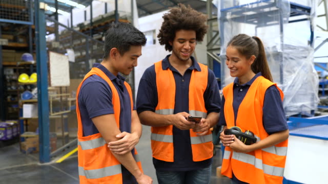 Warehouse workers looking at a cell phone
