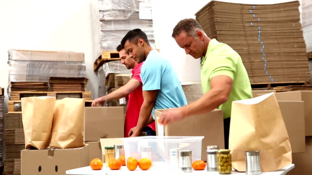 Warehouse workers packing up donation boxes video
