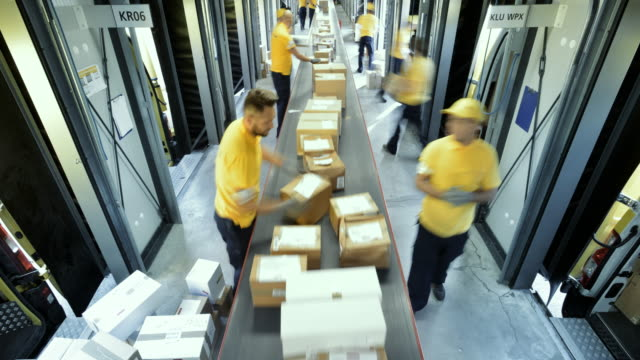vídeos de stock e filmes b-roll de time-lapse warehouse workers placing packages on the conveyor belt - cardboard box