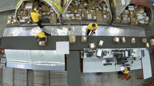 TIME-LAPSE Warehouse workers putting packages onto the conveyor belt Time-lapse wide right above shot of warehouse workers in yellow t-shirts putting packages onto the conveyor belt to be properly distributed. Shot in Slovenia. conveyor belt stock videos & royalty-free footage