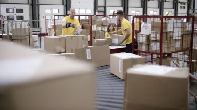 LD Warehouse workers scanning and stacking the packages travelling on the conveyor belt