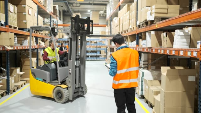 Warehouse workers. Manual workers in a warehouse. Made in Barcelona. forklift stock videos & royalty-free footage