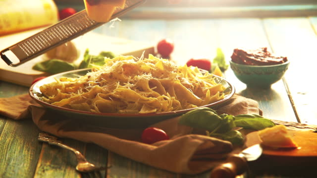 warm colors footage: hard cheese is grated on the beautiful plate of fresh pappardelle - pasta video stock e b–roll