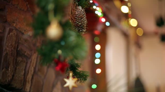 warme gemütliche stein kamin für weihnachten mit kranz, strümpfe, girlanden lichter dekoriert. mantelstück mit dekorationen für neujahrsferien. authentische festliche inneneinrichtung. dolly erschossen - girlande dekoration stock-videos und b-roll-filmmaterial