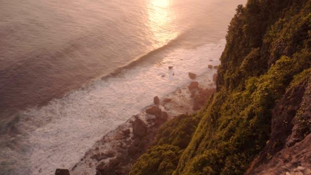 stockvideo's en b-roll-footage met warme zonsondergang of zonsopgang, oceaan met golven en rotsen - {{asset.href}}
