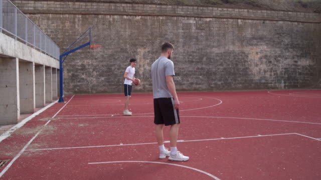 Warming up before amateur basketball match Group of young adults playing amateur basketball outdoor practice drill stock videos & royalty-free footage