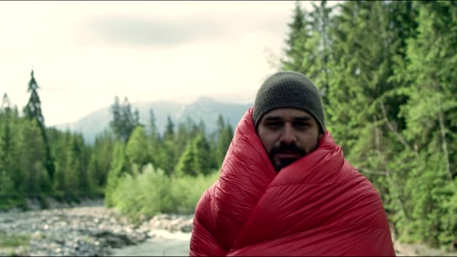 Warming up with sleeping bag. Springtime in mountains video