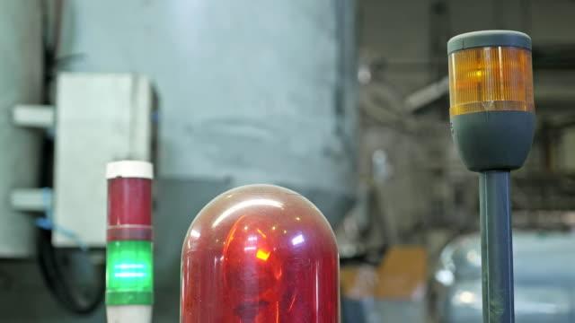 加工機の警告灯。トイレット ペーパー生産工場の大規模なワーク ショップでマシンのクローズ アップ赤点滅ランプ。金属キャビネットの赤いサイレン。作業エリアの安全性の警告灯。 - センサー点の映像素材/bロール