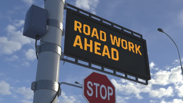 vídeos de stock, filmes e b-roll de aviso, trabalho rodoviário à frente, sinalização rodoviária com texto em execução, restrições de tráfego - sinal