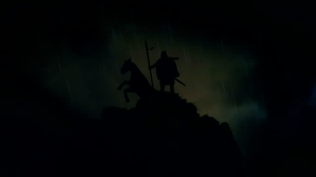 a warrior and his horse standing on a cliff under a lightning storm - битва стоковые видео и кадры b-roll