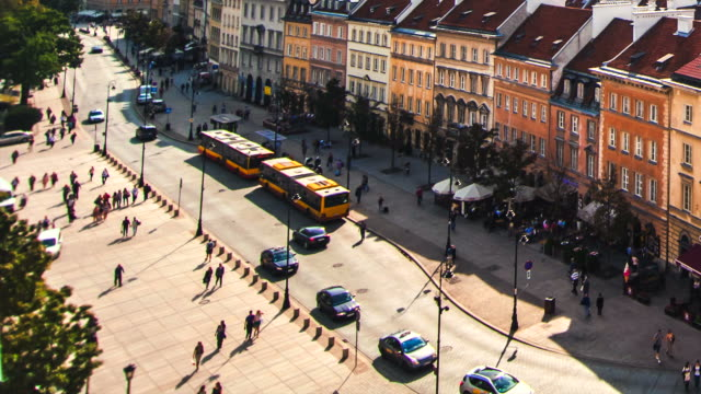 Warsaw Old Town city traffic with old buildings and modern buses, cars, people rushing in time lapse video