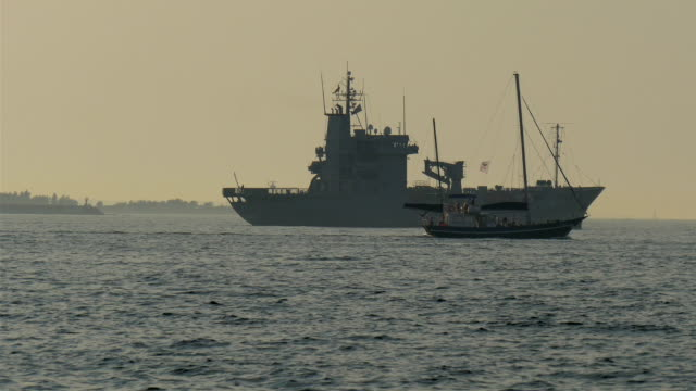 A warship on standy and a small viking boat crossing video