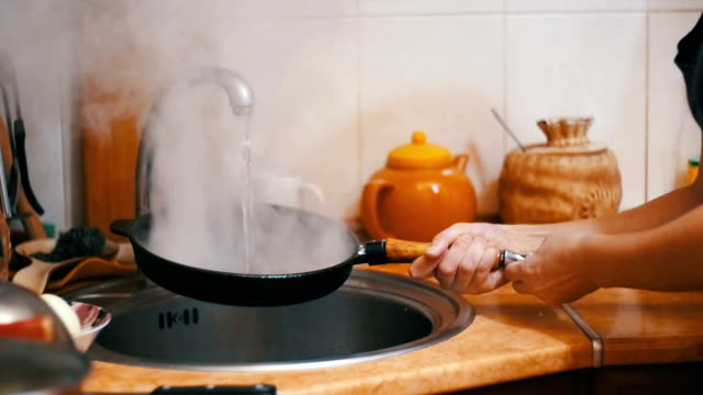 Wash Hot Frying Pan Turns a Jet of Cold Water into Steam in a Sink of Home Kitchen. Slow Motion video