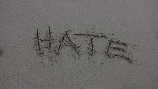 'hate' washed away on the beach - etnicitet bildbanksvideor och videomaterial från bakom kulisserna