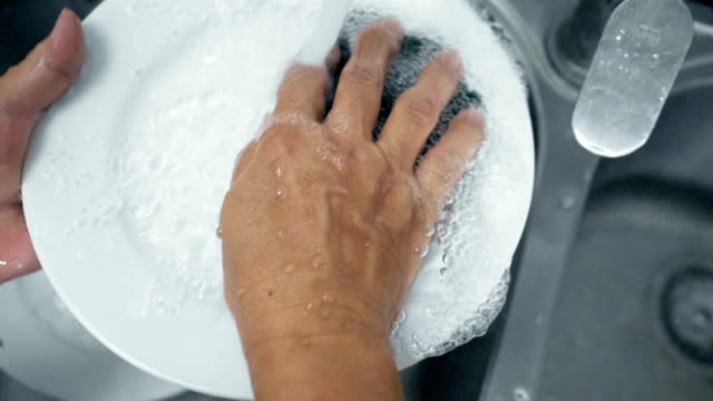 Washing at kitchen sink Washing at kitchen sink washing dishes stock videos & royalty-free footage
