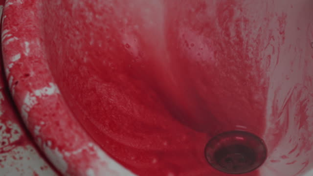 Washing away blood stains from a bathroom sink.