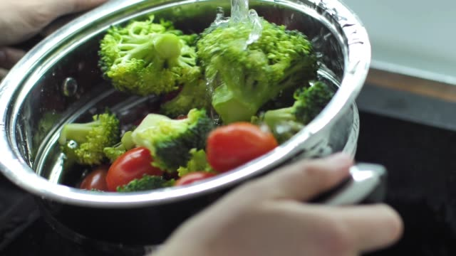 vídeos de stock e filmes b-roll de washing broccoli and cherry tomato slow motion video - vegetables