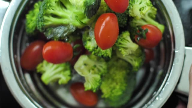 Washing broccoli and cherry tomato slow motion video video